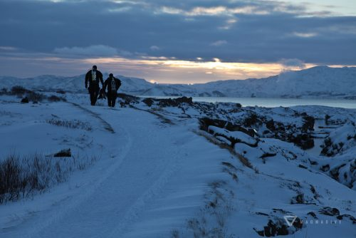 Divers walking through the snow at Silfra during the wintertime.